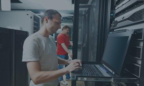 IT technician typing on server laptop