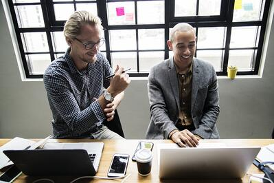 two male coworkers discussing technology support options over their laptops