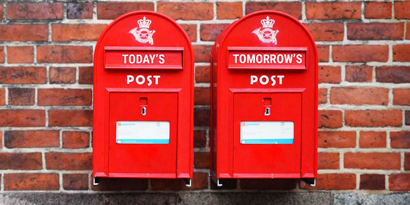 two retro uk mailboxes side by side against a brick wall prioritize tickets