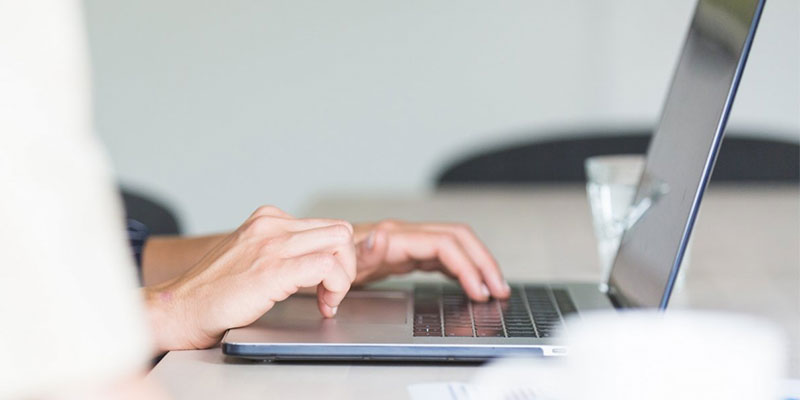 a low angle sideview of hands typing on laptop