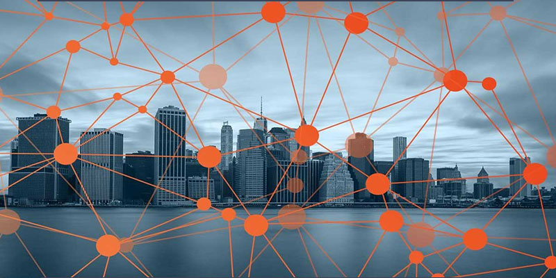 series of integrated orange dots against an overlaid city skyline with waterfront view