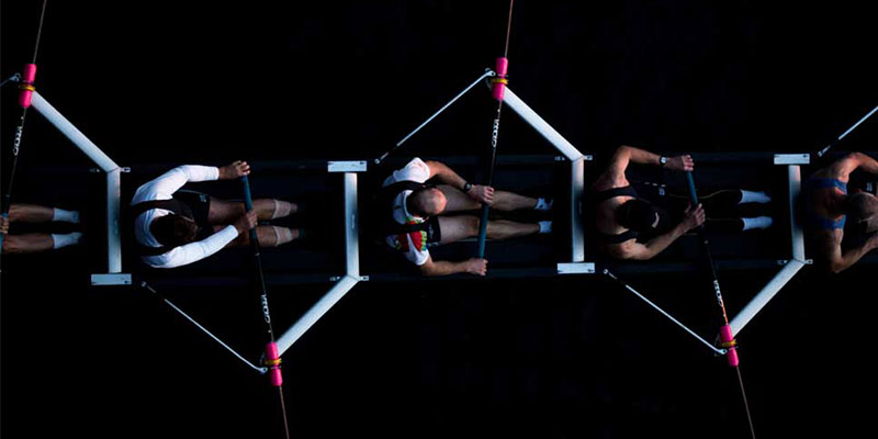 top view close up of a synchronized rowing team against dark background