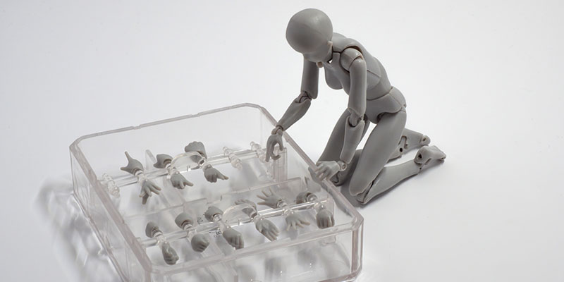 a grey miniature robotic humanoid model leans over subsitute hand replacements