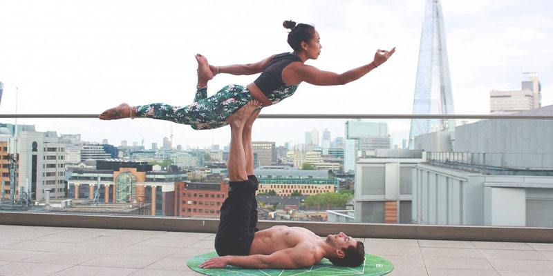 a physically fit man on his back legs up balancing a woman in yoga pose