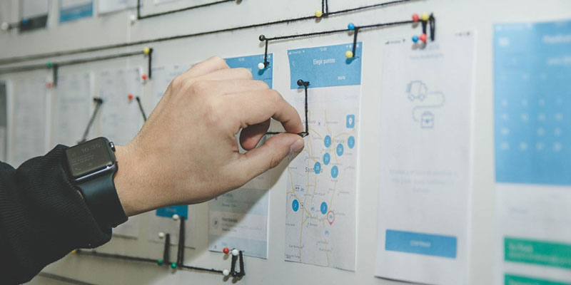 a hand placing a pin on mock-up of software ITSM UI